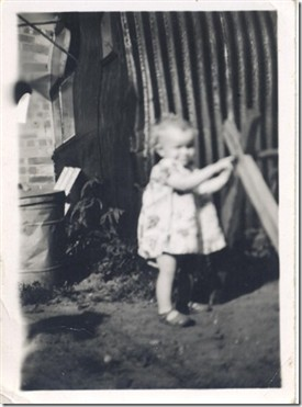 Photo:Linda toddling outside the hut where she was born