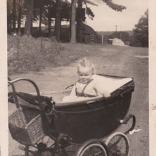 Photo:Baby Linda in her pram with the huts behind
